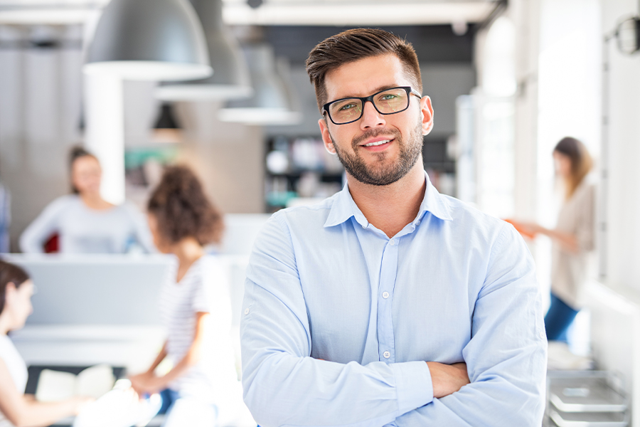 Business Insurance - Portrait of a Young Professional Businessman with Coworkers Blurred in the Background at the Office